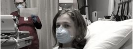 Young woman in hospital wearing face mask portraying suffering